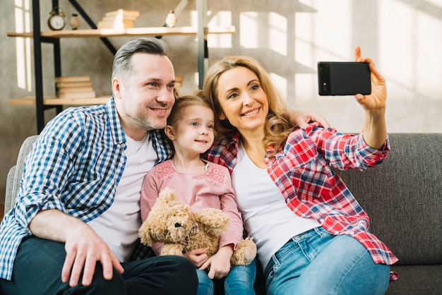 Happy family taking selfie on sofa