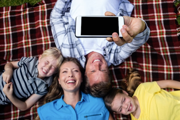Happy family taking a selfie while lying in the park