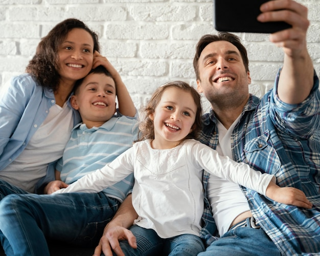 Happy family taking selfies medium shot