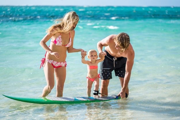 Happy family teaching the daughter to stand on the surf in the ocean. concept about family, sport, active people