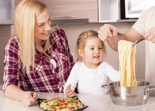 Famiglia felice e la loro piccola figlia che preparano gli spaghetti fatti in casa sul bancone della cucina