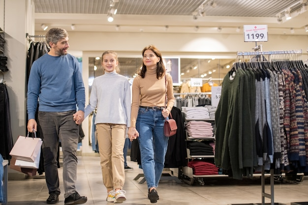 Happy family of three in casualwear holding by hands while moving along clothing department during seasonal sale period