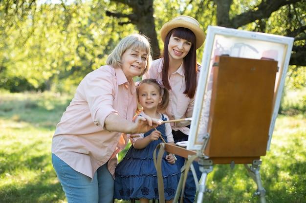 幸せな家族三世代の女性。屋外で絵を描く家族。春の庭のイーゼルに一緒に絵を描きながら、お母さんとおばあちゃんと楽しんでいるかわいい女の子。