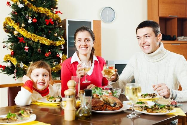 Una famiglia di tre felice che hanno cena di natale