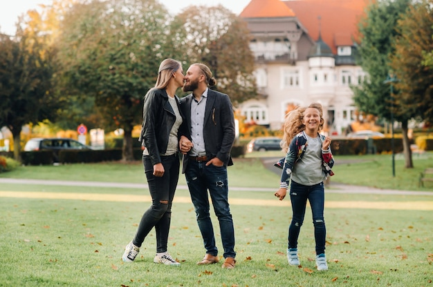 A happy family of three runs through the grass in austria's old town