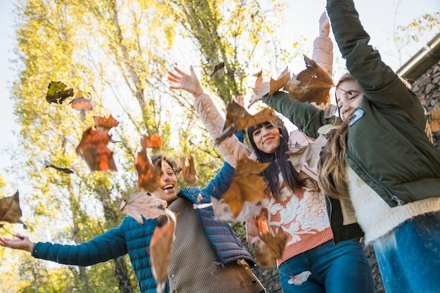 Счастливая семья, бросающая осенние листья в парке