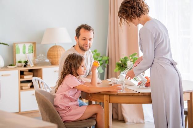 테이블에서 함께 행복 한 가족입니다. 엄마는 딸의 유리잔에 물을 붓습니다.