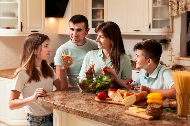 食糧を準備するキッチンで一緒に幸せな家族