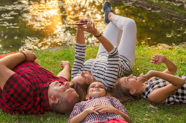 Happy family together laying on green grass and take a selfie with mobile phone