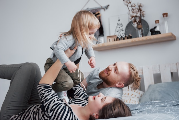 一緒に幸せな家族。母、父、子供の娘がお祝いの日に寝室でハグ