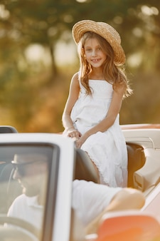 Счастливое семейное путешествие на машине в горы. люди веселятся в красном кабриолете. концепция летних каникул
