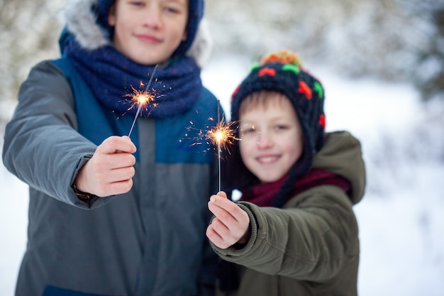 Happy family two brothers keep a sparklers or bengal fires outdoor in beautiful winter forest.