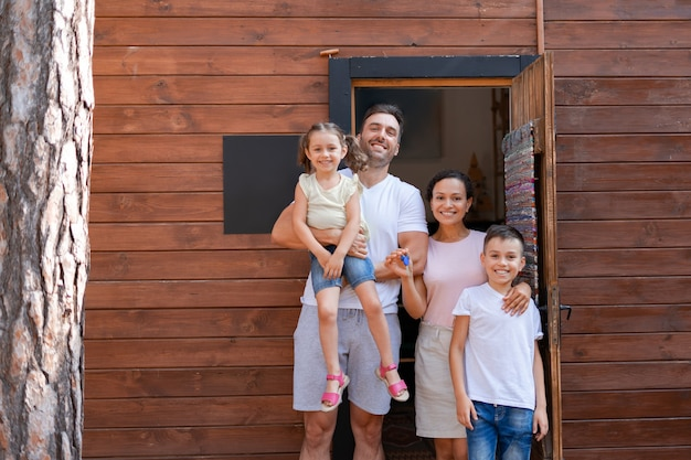 Happy family, two children and parents, stand at the door and look forward to moving to a new wooden house, where they will spend their summer