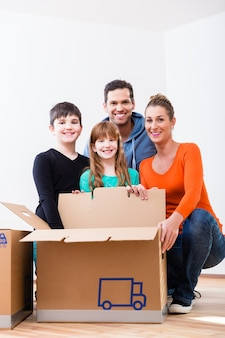 새 집에서 이동 상자를 풀고 행복 한 가족