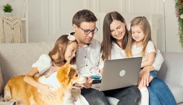 Счастливая семья использует ноутбук для покупок в интернете