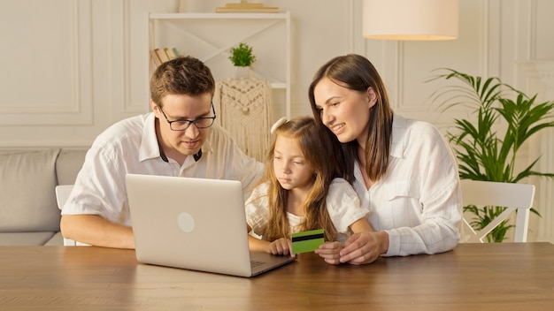 A happy family uses a laptop for online shopping sitting at home