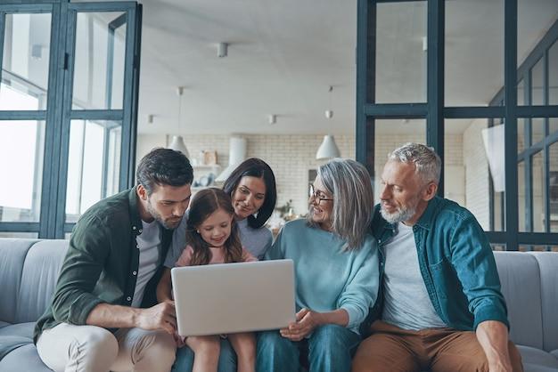 Счастливая семья, используя ноутбук и улыбаясь, проводя время дома вместе