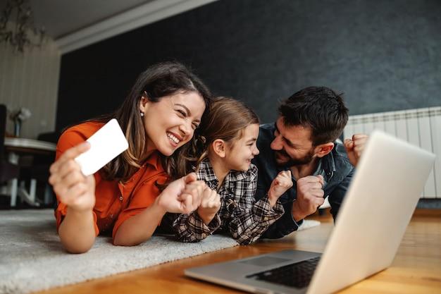 Счастливая семья, использующая ноутбук для покупок в интернете. они рады покупке. мама держит кредитную карту.