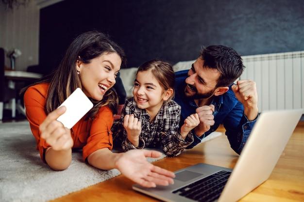 オンラインショッピングにラップトップを使用して幸せな家族。