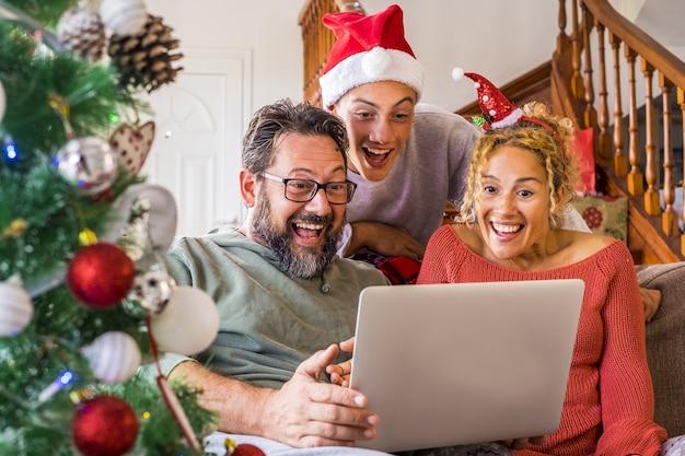 クリスマスの前夜にビデオチャットのためにラップトップを使用して幸せな家族。ビデオ会議でクリスマスを祝う家族。クリスマスの機会に近くの人や大切な人とおしゃべりする興奮した家族のビデオc