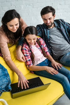 Happy family using a laptop high view
