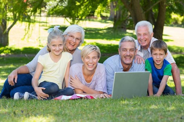 공원에서 노트북을 사용하는 행복한 가족