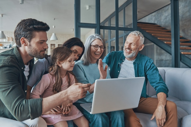 Happy family using laptop and smiling while spending time home together