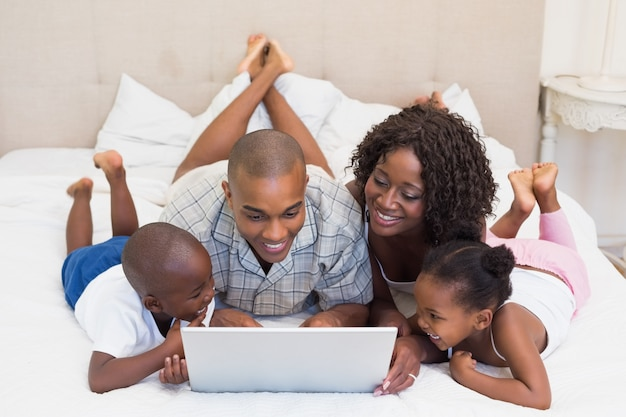 Happy family using laptop together on bed