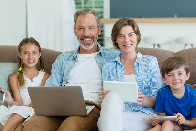 Happy family using mobile phone, digital tablet and laptop in living room