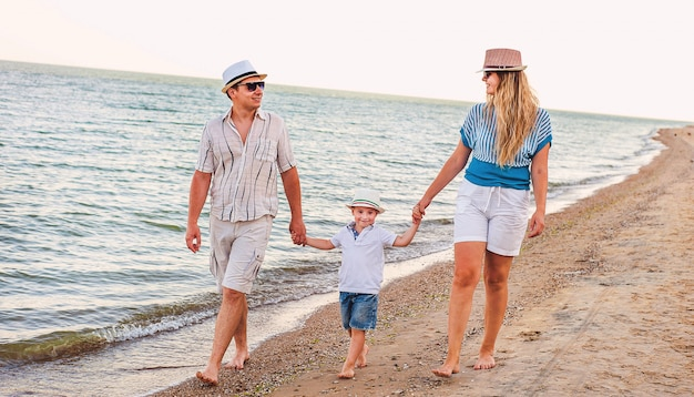 Happy family on vacation. mom, dad and a little son are walking along the seashore. traveling family.
