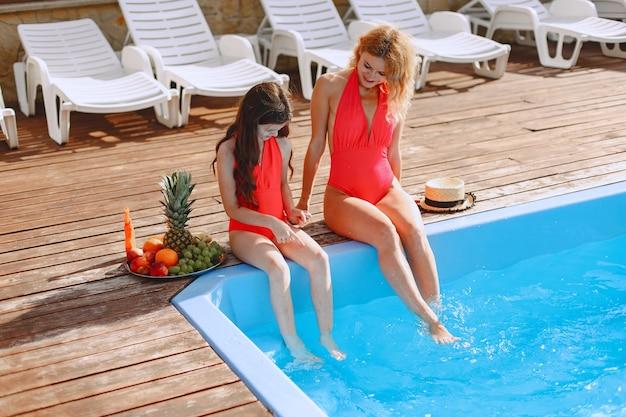 Famiglia felice in vacanza. madre e figlia in costume da bagno e occhiali da sole seduti a bordo piscina.
