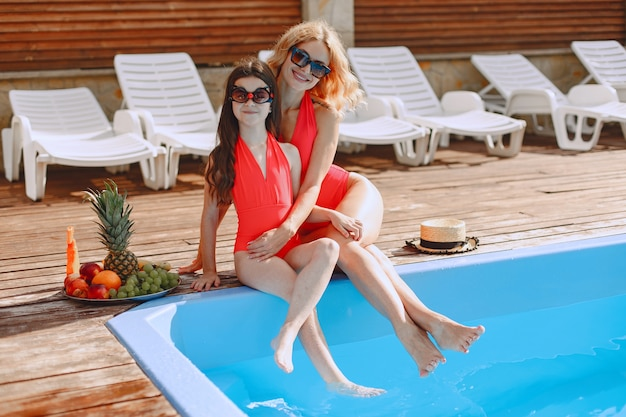 Happy family on vacation. mother and daughter in swimsuits and sunglasses sitting by the pool.
