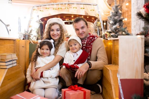 赤い車のトレーラーのピックアップでクリスマスを待っている幸せな家族。メリークリスマス、そしてハッピーニューイヤー
