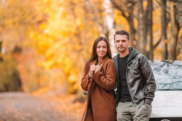 Happy family walking in autumn park on sunny fall day
