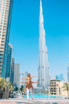 Happy family walking in dubai with burj khalifa skyscraper in the background.
