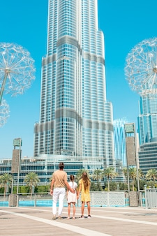 Happy family walking in dubai with burj khalifa skyscraper