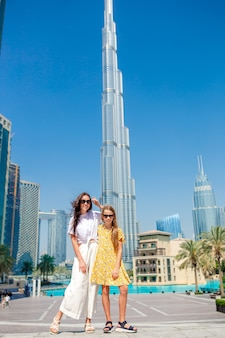 Happy family walking in dubai with skyscrapers