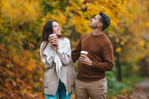 晴れた秋の日に秋の公園を歩く幸せな家族