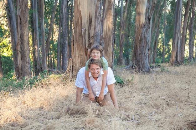 晴れた日に公園を歩いて幸せな家族。愛らしい幼児の男の子を持つ父