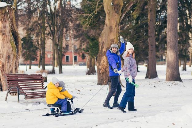 Счастливая семья гуляет в зимнем парке вместе, двое взрослых мужчина и женщина и двое детей