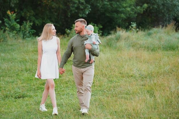 日没時に自然の中でフィールドを歩く幸せな家族