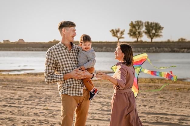 Счастливая семья, идущая на песчаном пляже. отец, мать держит маленького сына на руках и играет с воздушным змеем.