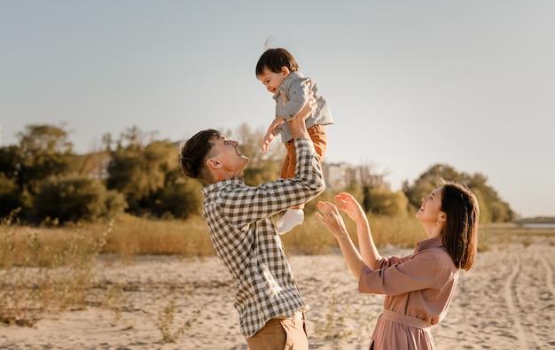 강 모래 해변에 산책하는 행복 한 가족. 아버지, 어머니 손에 아기 아들을 들고 함께가. 배면도. 가족 관계 개념.