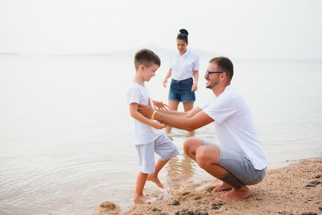 Счастливая семья, гуляя по пляжу Premium Фотографии