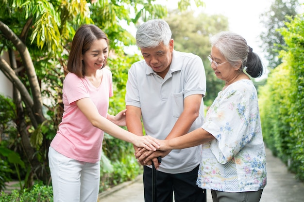 Happy family walking together in the garden. old elderly using a walking stick to help walk balance. concept of  love and care of the family and health insurance for family