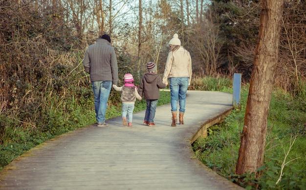 Счастливая семья гуляет вместе, держась за руки по деревянной дорожке в лесу