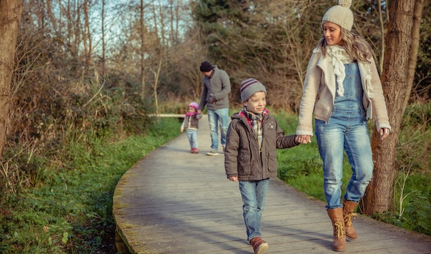 森への木製の小道を手をつないで一緒に歩いている幸せな家族