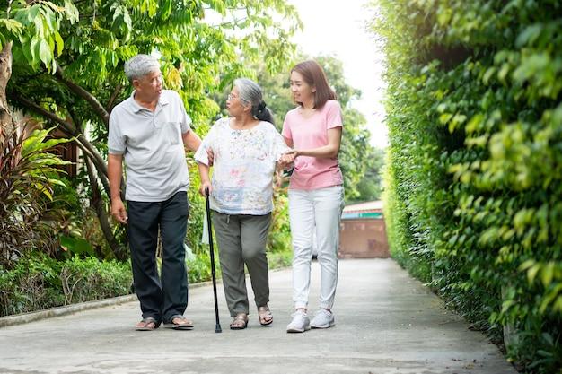 庭で一緒に歩いている幸せな家族。歩行バランスを助けるために杖を使用している高齢者。家族の愛とケアの概念と家族の健康保険