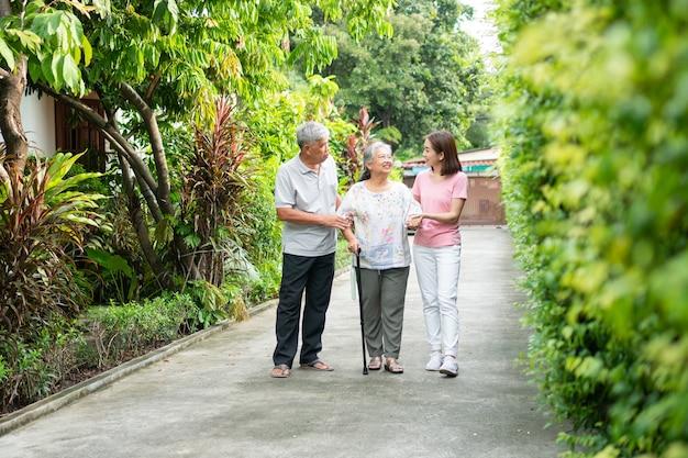 庭を一緒に歩く幸せな家族杖を使って歩くバランスをとる老人