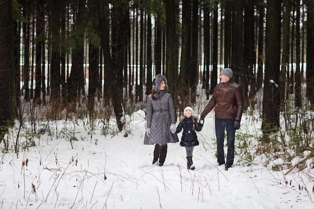 Happy family walking in a winter park.